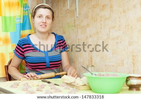 Woman making russian meat dumplings (pelmeni) in her kitchen - stock photo