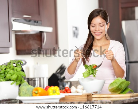 Woman making salad in kitchen. Healthy eating lifestyle concept with beautiful young woman cooking in her kitchen. - stock photo