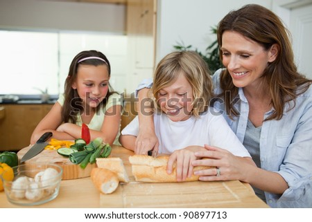 Woman making sandwiches together with her children - stock photo
