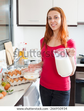 Woman making scrambled eggs with milk in home kitchen