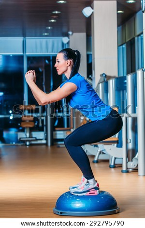 Woman making squats on balance trainer dsd sdv  sdv  sdv  - stock photo