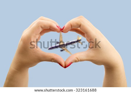woman making the heart shape with her hands and the airplane in the middle  - stock photo