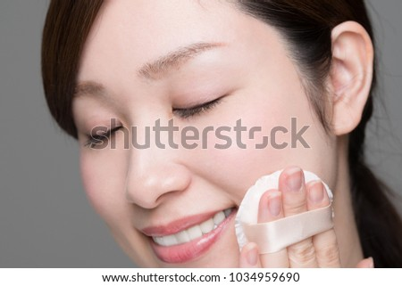 Woman making up makeup, foundation, puff, sponge