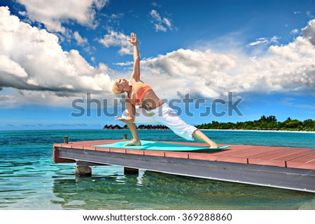 woman making yoga exercise at a lake - stock photo