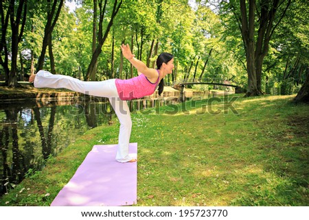 woman making yoga exercise in an old park - stock photo
