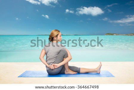 woman making yoga in twist pose on mat
