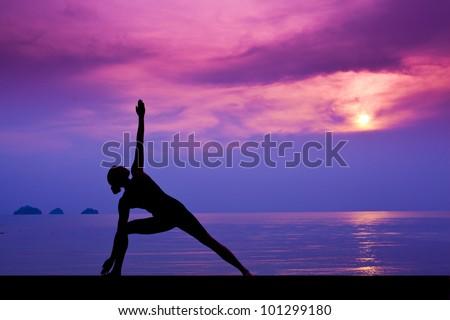Woman making yoga on the beach - stock photo