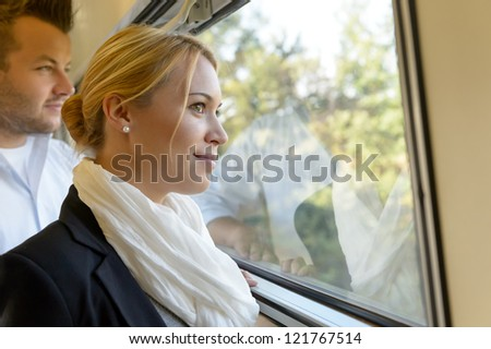 Woman man looking out the train window smiling thinking friends - stock photo