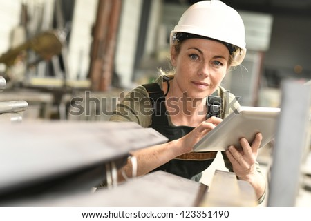 Woman manager in warehouse checking stock