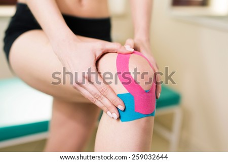 Woman massages injured knee with kinesiotaping - stock photo