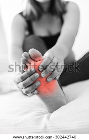 Woman massaging her painful foot, red highlighted on pain area - stock photo