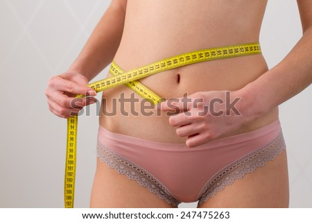 woman measures the waist with a yellow measuring tape