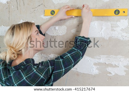 woman measuring a wall with spirit level in room - stock photo