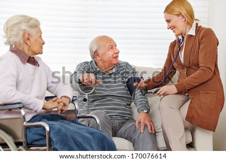 Woman measuring blood pressure on her senior parents at home - stock photo