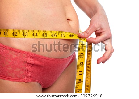 Woman measuring fat abdomen. Overweight and weight loss concept. - stock photo