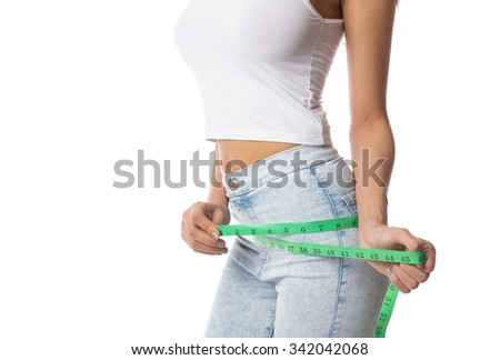 Woman measuring her hip. Weight loss concept, isolated on white background. - stock photo