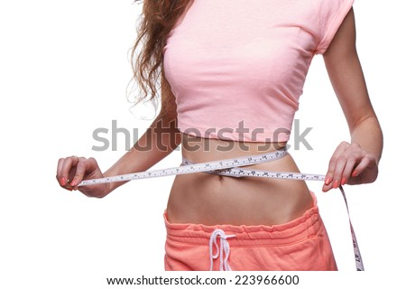 Woman measuring her slim body isolated on white background. Cropped image. - stock photo