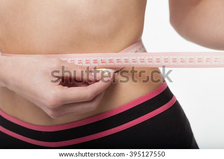 Woman measuring her slim body on white background. Health concept. - stock photo