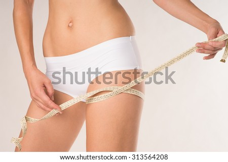 Woman measuring her thigh circumference / thigh circumference - stock photo