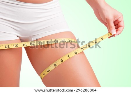 Woman measuring her thigh with a yellow measuring tape - stock photo