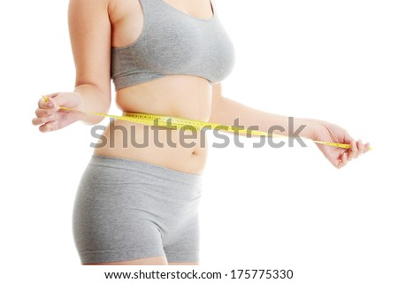 Woman measuring her waist isolated on white  - stock photo