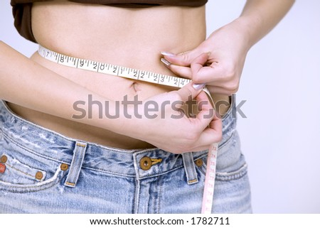 woman measuring her waist wearing jeans shorts