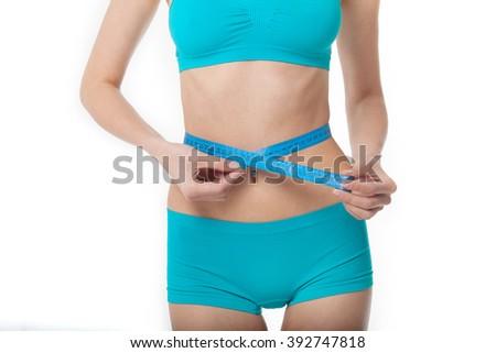 Woman measuring her waistline. Diet. Perfect Slim Body. Sport woman in blue. - stock photo
