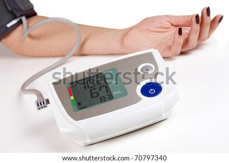 Woman measuring his own blood pressure on white background - stock photo
