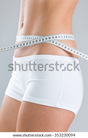 Woman measuring stomach volume with measuring tape