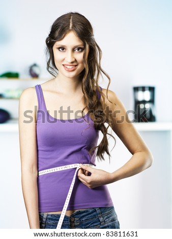 Woman Measuring Waist in kitchen - stock photo