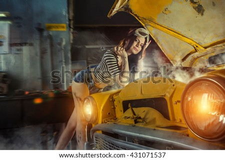 Woman mechanic in sexy shirts is repairing an old car with the wrench.