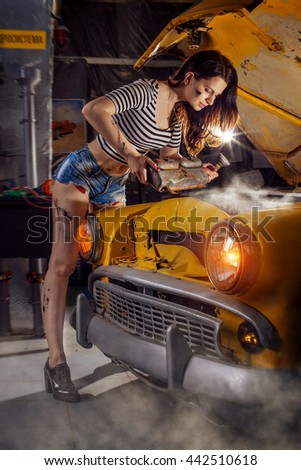Woman mechanic in sexy shirts is repairing the engine of an old car.