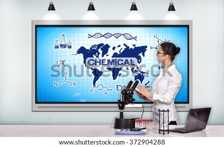 woman medical or scientific researcher in laboratory and looking on tv screen with chemical concept - stock photo