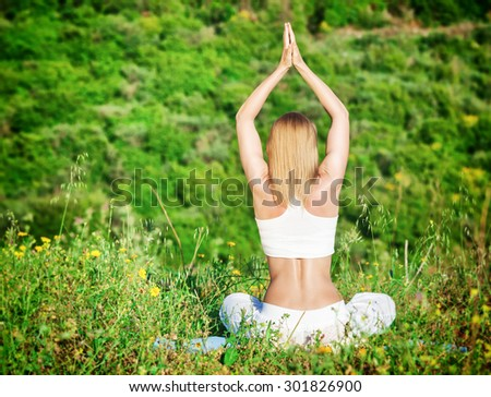 Woman meditate outdoors, rear view of slim blond female sitting on fresh green grass field in the park and doing yoga exercise, peace and mental health concept - stock photo