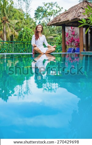 Woman meditating at pool side. Copy space in the bottom of the photo - stock photo