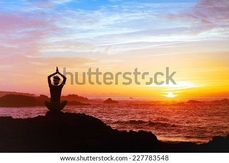 woman meditating at sunset, silhouette of person practicing yoga, mental health concept