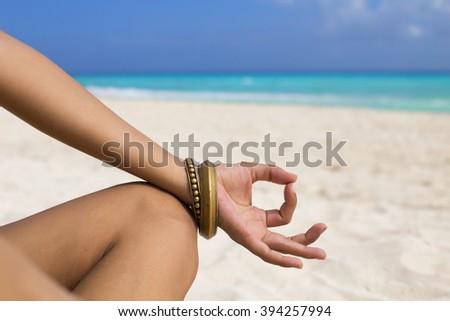 Woman meditating at the beach in a yoga retreat. Playa del Carmen, Mexico. - stock photo
