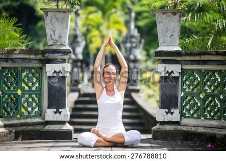 woman meditating doing yoga - stock photo