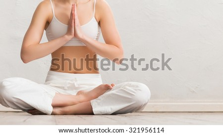 Woman meditating in a gym. Yoga exercise.  - stock photo