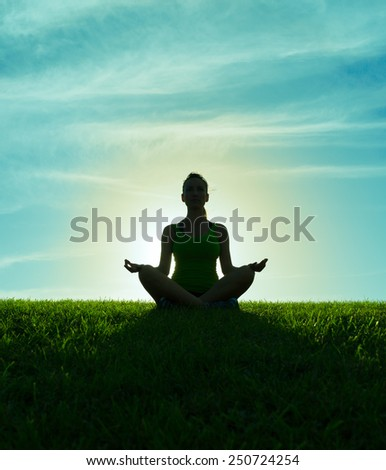 Woman meditating in a yoga pose - stock photo