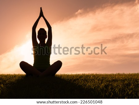 Woman meditating in a yoga pose outdoors - stock photo