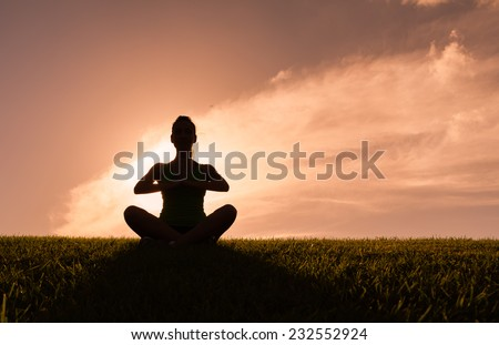 Woman meditating in a yoga pose outdoors. - stock photo