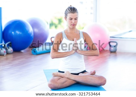 Woman meditating in fitness studio on yoga mat - stock photo