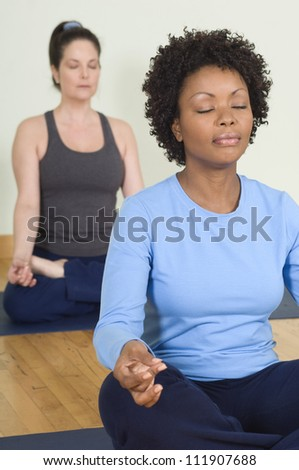 Woman meditating in lotus position with closed eyes - stock photo