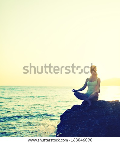 woman meditating in  lotus yoga on  coast of  sea on the beach - stock photo