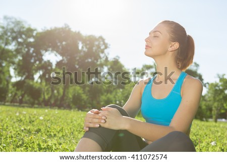 Woman meditating in park - stock photo