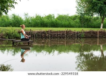 Woman meditating in pose of lotus Yoga - stock photo
