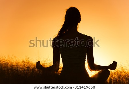 Woman meditating in the park.  - stock photo