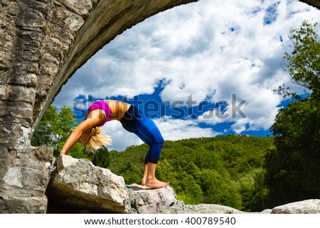 Woman meditating in yoga bridge pose under a medieval stone bridge near river in beautiful mountains. Motivation and inspiration fit and exercise. Healthy lifestyle in nature, fitness concept. - stock photo