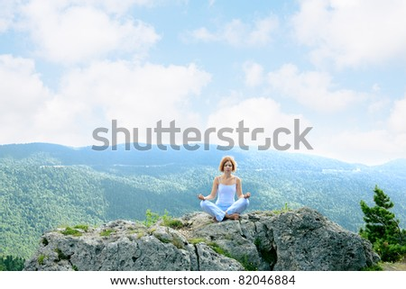 woman meditating on a background of mountains - stock photo